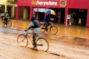 Bicyclists traveling down a street in the rain.