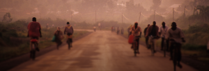 Bicyclists traveling down a dirt road.