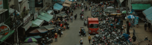 Crowded street filled with parked motorbikes and street vendors.