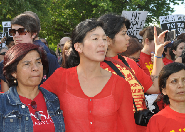 Aj-jen Poo of the National Domestic Workers Alliance standing amongst other protesters.