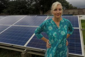 Woman posing in front of a solar paneled mini-grid.