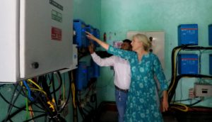 Woman pointing to a mini-grid as a man looks on.