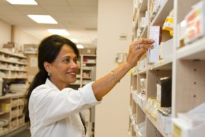 Pharmacist stocking shelves with medicine.