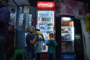 Children drinking soda from a mini-grid powered shop in Derni, Bihar.