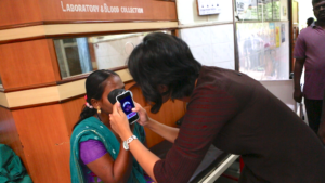 Woman checking a patient's right eye with a phone app