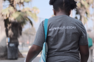 Girl wearing a shirt with #GivingTuesday printed on the back