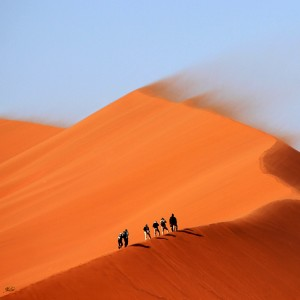People climbing a sand dune in the desert.