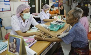 Elderly man receiving medical attention from a nurse at Dontal hospital in northern Thailand.