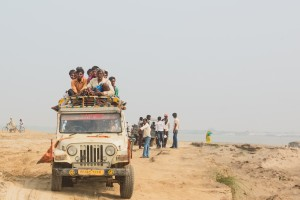 Villagers cram together on the roof of a vehicle in order to travel between their island and the nearby city of Patna.
