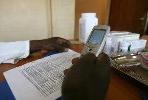 Rwanda lab technician at the Masaka hospital inserting data on his mobile phone.