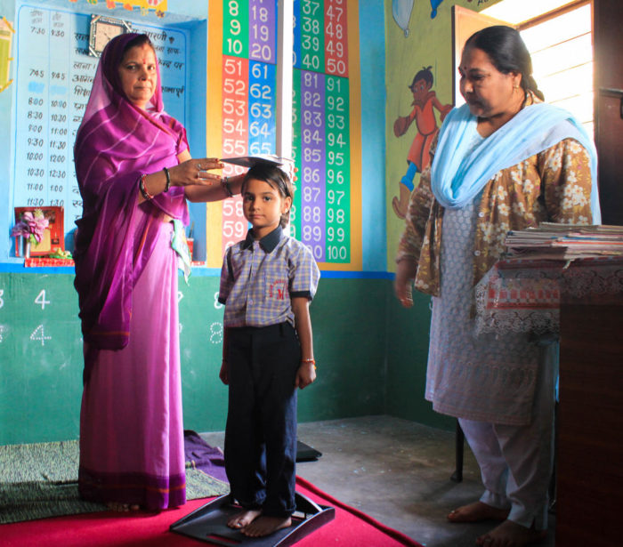 Child attending school in India with two female teachers looking on.