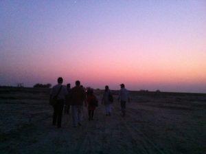 Group of people walking through the desert at sunset.