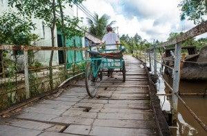 Man travels down a road rebuilt after a bad flood.