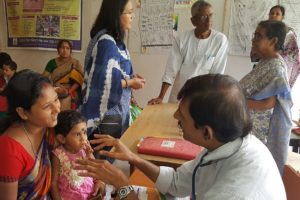 Medical professionals assisting mothers with young children in India.