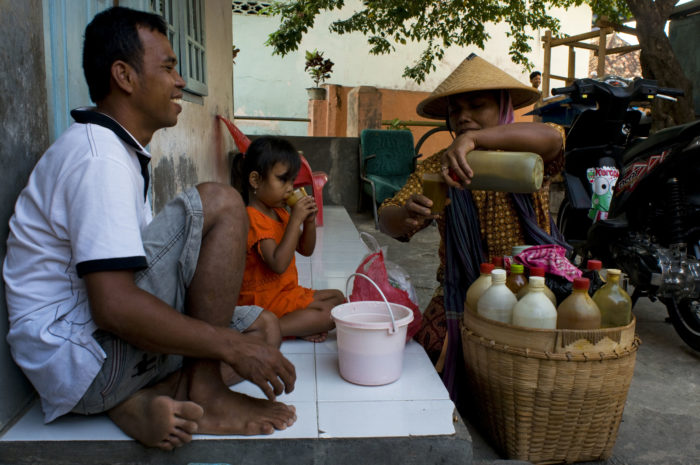 Street vendor sells product to a man and child.
