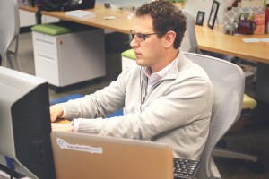 Man at his computer wearing a headset.