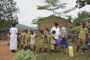 Healthcare workers in Africa help children properly wash their hands.