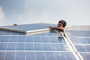 Man installing the first solar panel in a power grid.