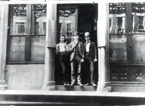 Black and white historical photo of people standing outside Pearl Street Station.