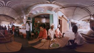 People eating at an outdoor pavilion in India.