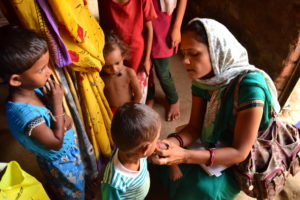 A community health worker in Barwani, India, crouches down to measure the upper arm circumference of a young boy to determine his nutrition status. © 2013 Chelsea Hedquist, Courtesy of Photoshare