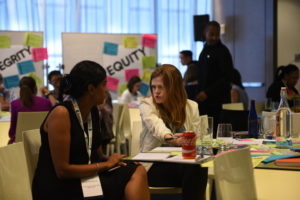 Two female Rockefeller Foundation employees in a discussion at the All Staff event.