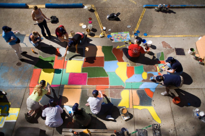Volunteers paint a map of the United States on a sidewalk.