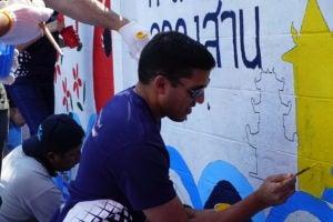 Dr. Rajiv Shah painting a community center in Bangkok, Thailand.
