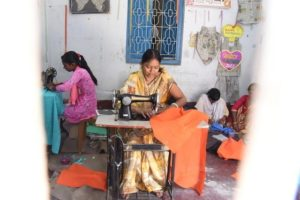 Three women using sewing machines to create dresses from colorful Indian fabric