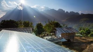 Village huts having solar panels installed with mountains in the distance.