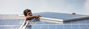Man installing the final module on a solar panel.