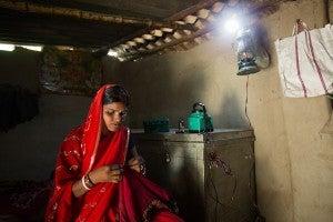 Woman stitching under a smart powered lamp.