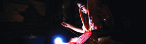 Woman sewing by a lamp powered by a solar mini-grid.
