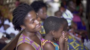 Mother holding her child at a congregation.