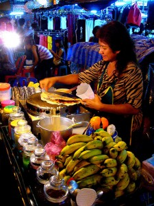 Street vendor cooking food at her stand.