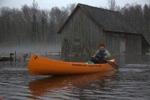 Man kayaking on an orange boat following a flood.