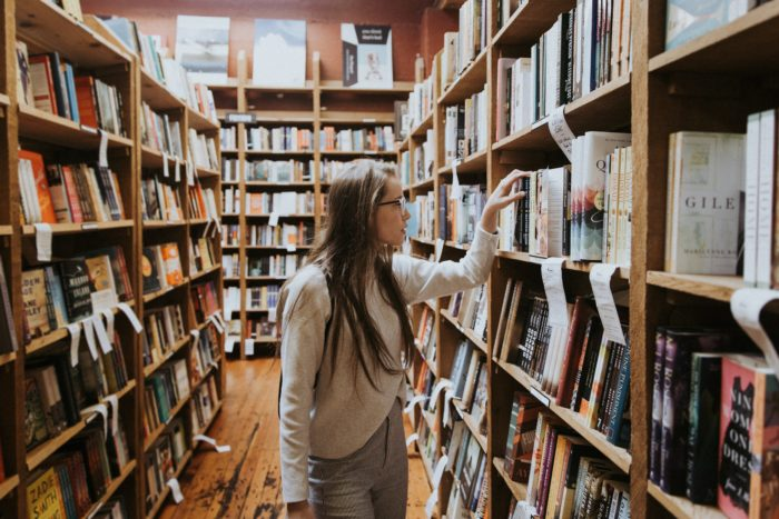 Women selecting a book off the shelf at a bookstore.