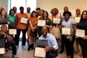 Image of a group of individuals holding their graduation certificates.