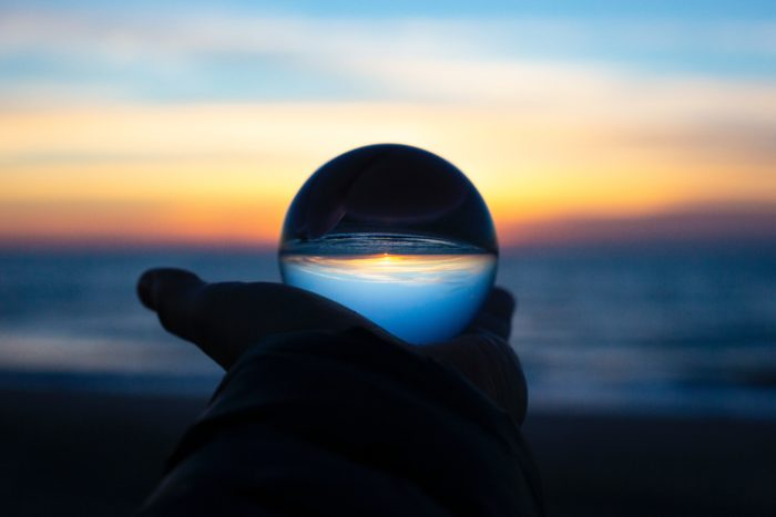 Hand holding a lens displaying a body of water at sunset.