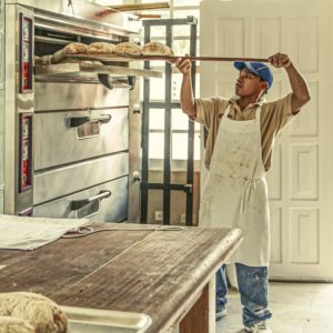 Man baking bread in the oven.