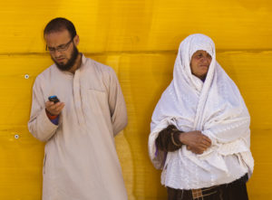 Man and a woman standing in front of a yellow wall.
