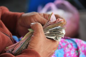Woman holding a pile of crumpled bills.
