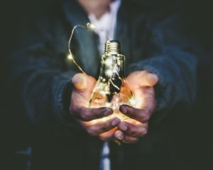 Person holding a light-bulb.