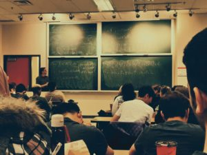 Professor giving a lecture to a crowded classroom.