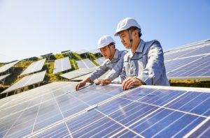 Workers inspect a solar panel mini-grid.