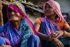 Two elderly women sitting side-by-side.