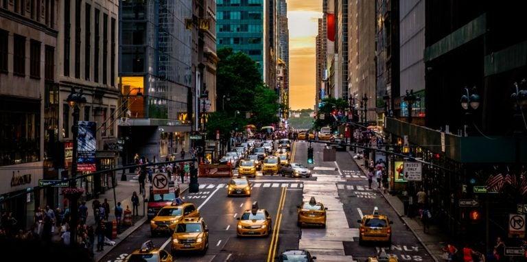 Bustling city street at sunset.